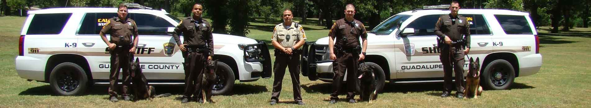 Guadalupe county officers standing next to their K9's.